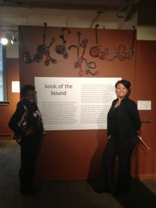 Thamar Theodore and museum staffer Leilani Lewis stand by the Book of the Bound exhibit.